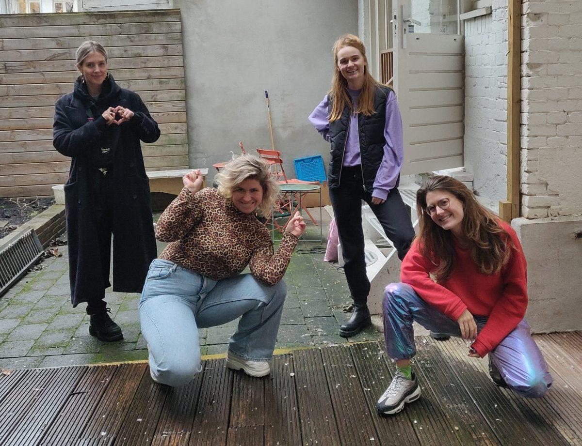 Nellie die een hartje vormt met haar vingers), Marie Lotte die naar Nellie en Laura achter haar wijst), Laura en Nydia poseren in de tuin van de studio van Dag en Nacht Media